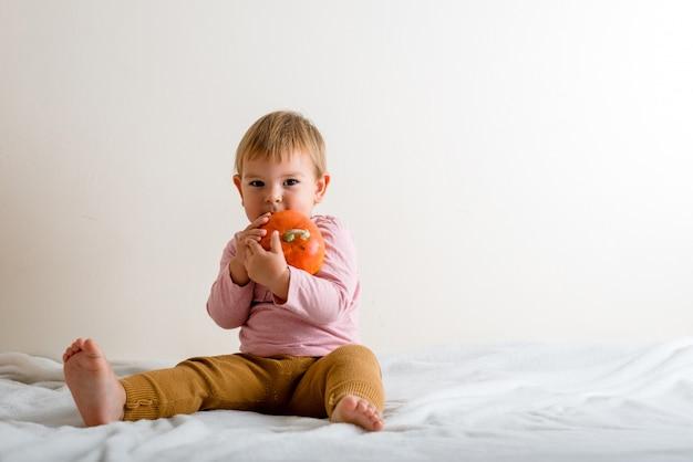 Jolie petite fille étreignant une citrouille sur un lit à l'intérieur. fond