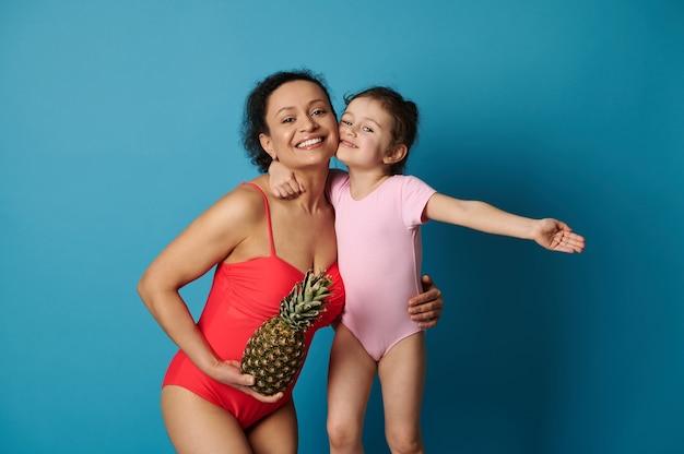 Une jolie petite fille étreignant sa mère avec un ananas dans ses bras, tous deux en maillot de bain.