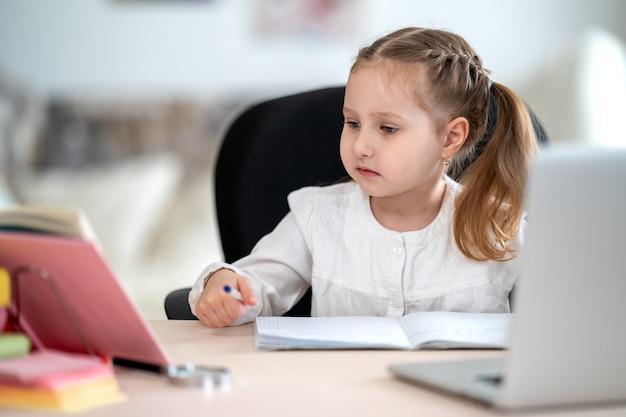 Jolie petite fille, faire ses devoirs, écrire dans un cahier, utiliser un ordinateur portable, e-learning