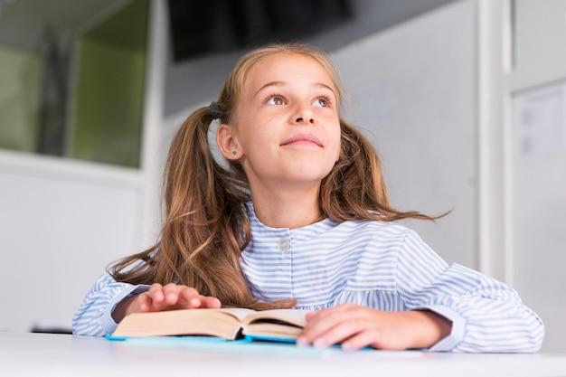 Jolie petite fille en faisant attention en classe