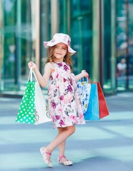 Jolie petite fille en faisant du shopping. portrait d'un enfant avec des sacs à provisions. achats. fille.