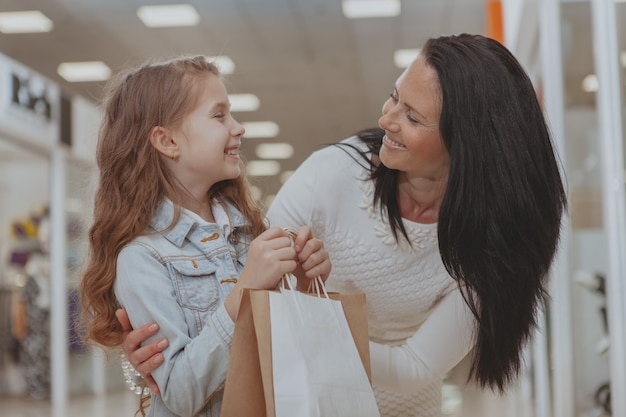 Jolie petite fille faisant des emplettes au centre commercial avec sa mère