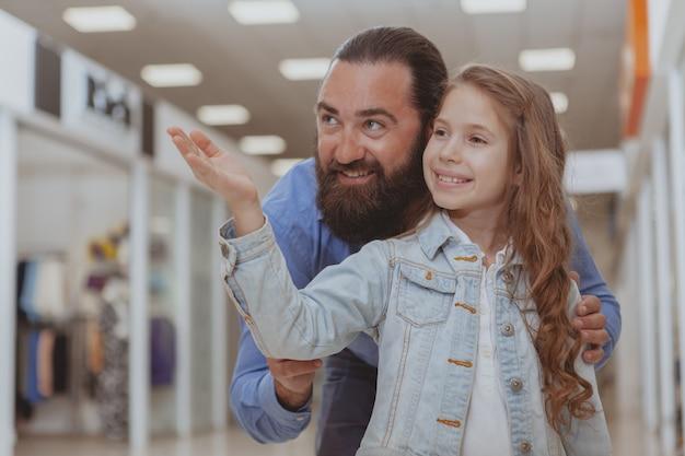 Jolie petite fille faisant des emplettes au centre commercial avec son père