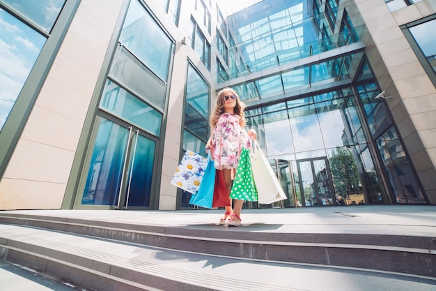 Jolie petite fille en faisant les magasins. portrait d'un enfant avec des sacs à provisions. achats. fille.
