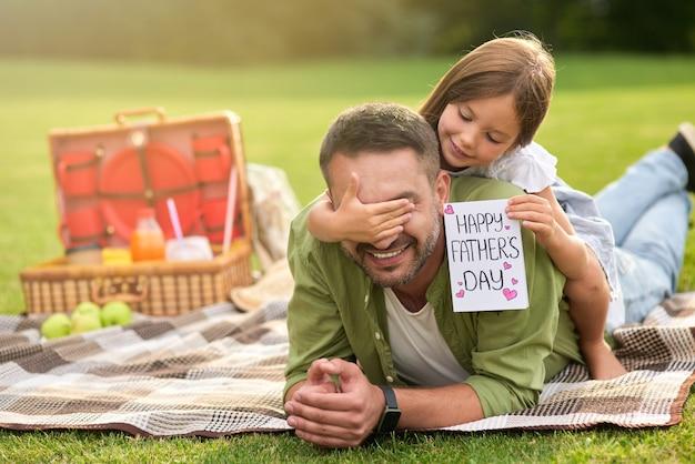 Jolie petite fille faisant à son père une surprise en lui donnant une carte postale faite à la main papa et fille