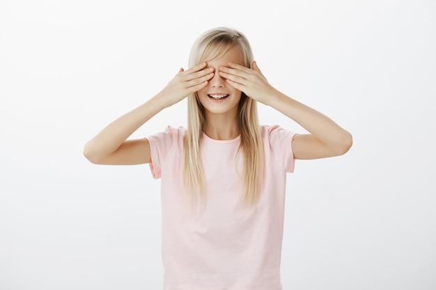 Jolie petite fille ferme les yeux, joue à cache-cache