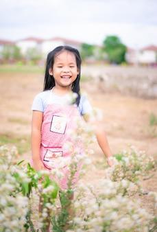 Jolie petite fille avec des fleurs d'herbe dans le parc