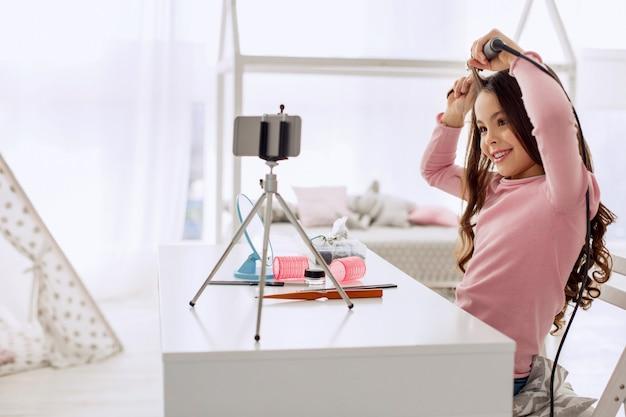 Jolie petite fille frisant une mèche de ses cheveux devant la caméra