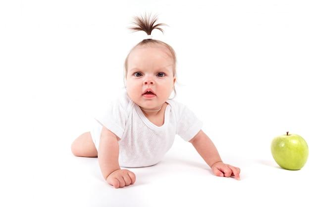 Jolie petite fille gaie en chemise blanche près de pomme