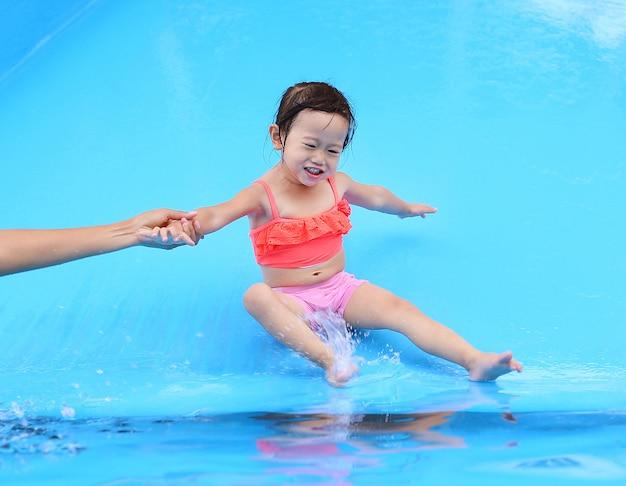 Jolie petite fille glissant dans la piscine en plein air