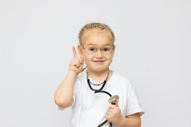 Jolie petite fille habillée comme un médecin regardant la caméra avec un sourire joyeux doigt vers le haut