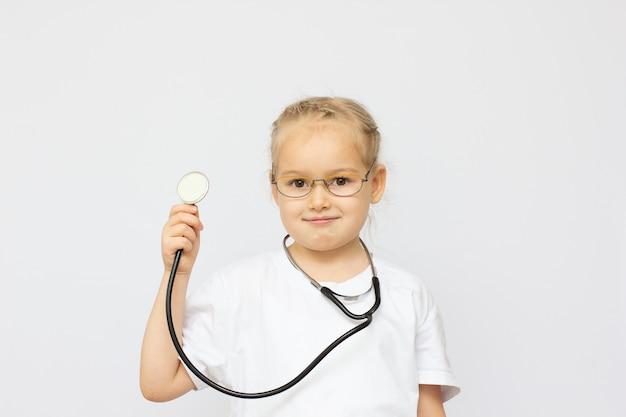 Jolie petite fille habillée comme un médecin regardant la caméra avec un sourire joyeux