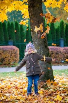 Jolie petite fille heureuse de 3-4 ans jouant dans le parc en automne. chute des feuilles d'automne.