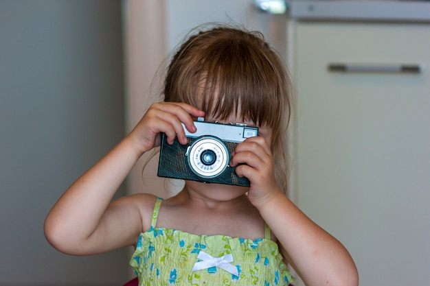 Jolie petite fille heureuse avec appareil photo vintage