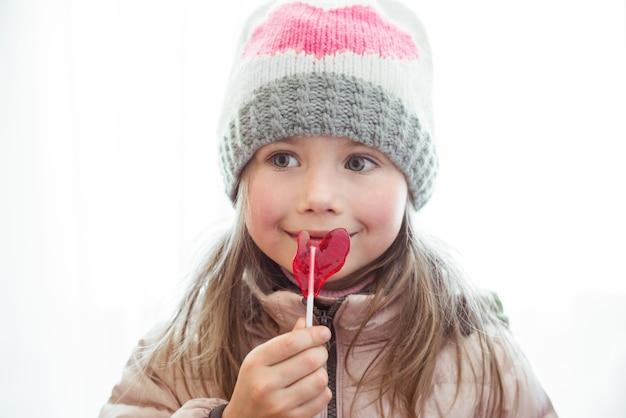 Jolie petite fille heureuse avec des bonbons de sucette avec copyspace