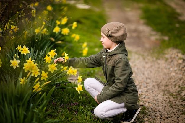 Jolie petite fille heureuse dans le pays du printemps sentant les jonquilles jaunes