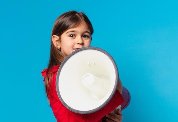 Jolie petite fille heureuse expression et tenant un mégaphone