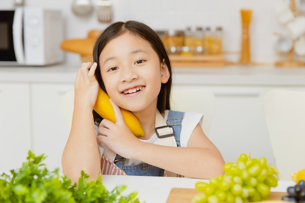 Jolie petite fille heureuse de jouer avec un portrait de banane souriant à la cuisine à la maison