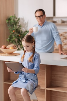 Jolie petite fille impliquée assis à la maison et jouer à des jeux sur tablette pendant que grand-père se repose