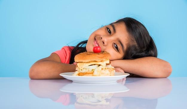Jolie petite fille indienne ou asiatique mangeant un savoureux hamburger, sandwich ou pizza dans une assiette ou une boîte. debout isolé sur fond bleu ou jaune.