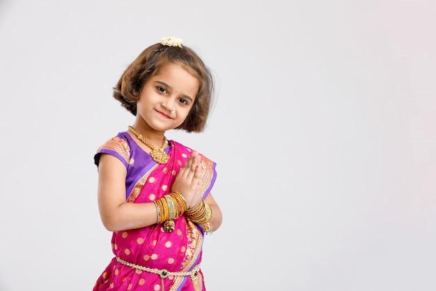 Jolie petite fille indienne / asiatique en priant pose