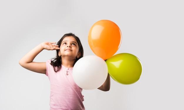 Jolie petite fille indienne avec des ballons tricolores - saluant le drapeau national et célébrant l'indépendance ou le jour de la république de l'inde