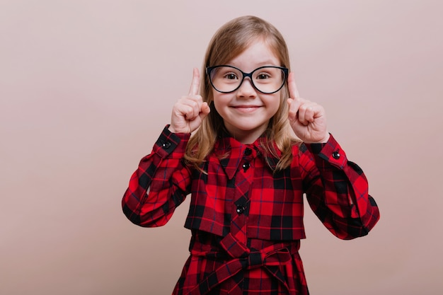 Jolie petite fille intelligente debout sur un mur beige tenant de gros finfer et regardant la caméra avec le sourire