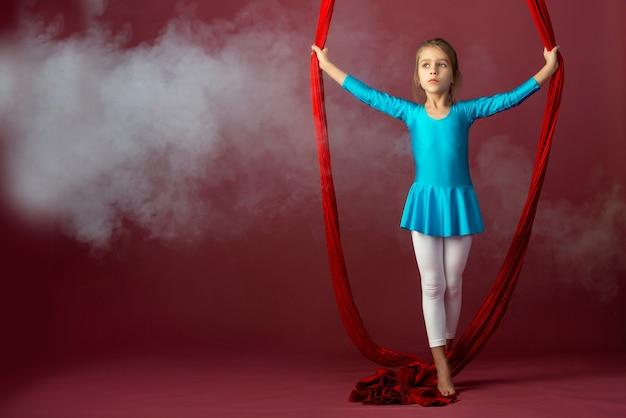 Une jolie petite fille intrépide dans un costume de gymnastique bleu montre un ruban rouge aérien de cascade entouré de fumée sur un fond pâle. concept de gymnastes acrobates avancés