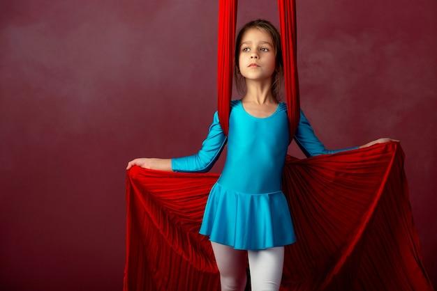 Jolie petite fille intrépide dans un costume de gymnastique bleu montre un ruban rouge aérien stunt