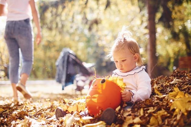 Jolie petite fille jouant dans les feuilles au parc d'automne avec ses parents.