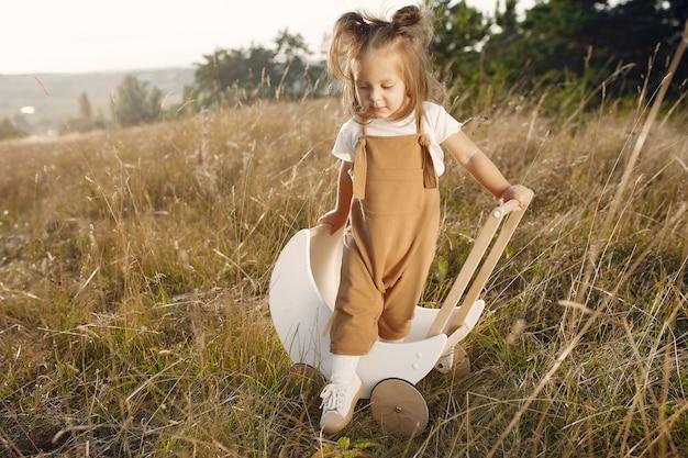 Jolie petite fille jouant dans un parc avec chariot blanc