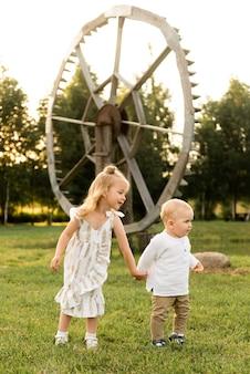 Jolie petite fille jouant avec son frère à l'extérieur par une journée ensoleillée