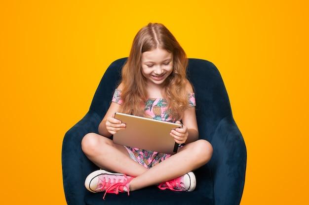 Jolie petite fille jouant avec une tablette assise dans la chaise sur un mur jaune