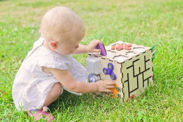 Jolie petite fille joue avec busiboard à l'extérieur sur l'herbe verte. jouet éducatif pour les tout-petits. fille a ouvert la porte au cube de planche.
