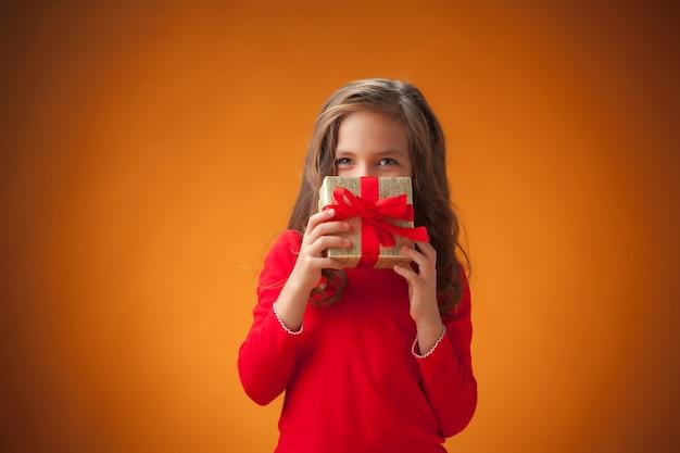 La jolie petite fille joyeuse sur fond orange