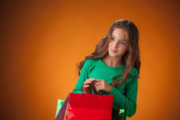 La jolie petite fille joyeuse avec des sacs à provisions