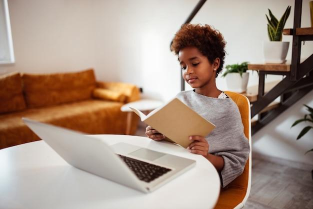 Jolie petite fille lisant un livre à la maison.