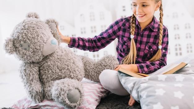 Jolie petite fille lisant un livre avec son ours en peluche