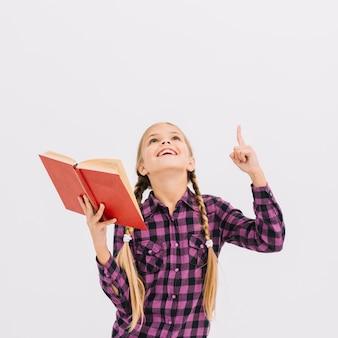 Jolie petite fille avec un livre pointant vers le haut