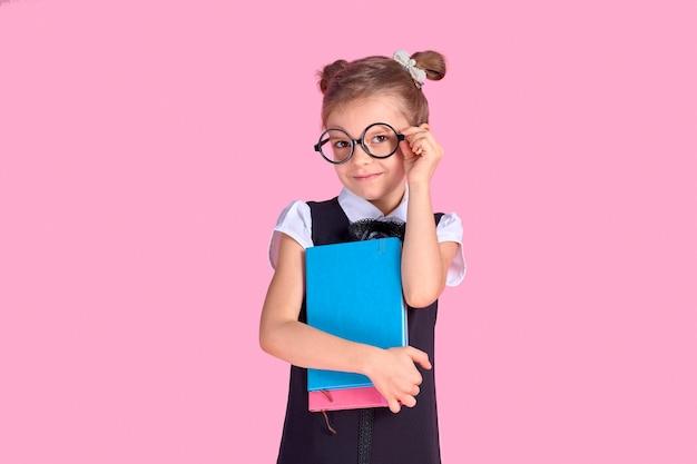 Jolie petite fille avec des lunettes et des livres sur l'espace rose, espace pour le texte