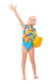 Jolie petite fille en maillot de bain bleu et un gilet de sauvetage coloré tiennent une serviette jaune