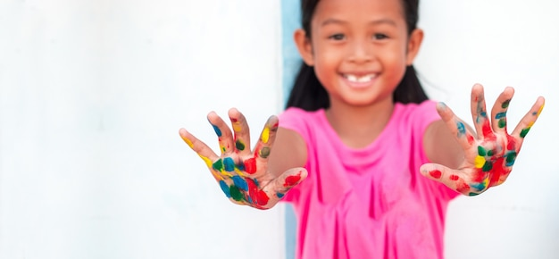 Jolie petite fille avec des mains peintes colorées sur fond de mur