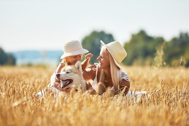 Jolie petite fille avec maman et chien sur champ de blé. heureuse jeune famille profiter du temps ensemble à la nature