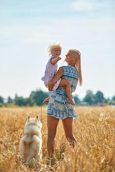 Jolie petite fille avec maman et chien sur champ de blé
