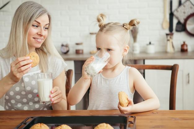 Jolie petite fille et maman mangeant des biscuits fraîchement préparés avec du lait dans la cuisine. famille heureuse. tonifiant.