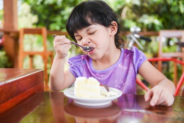 Jolie petite fille mange un gâteau