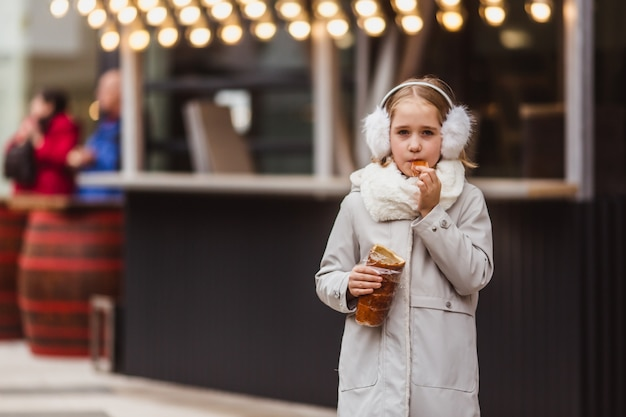 Une jolie petite fille mange une pâtisserie traditionnelle hongroise sur le marché de rue en hiver