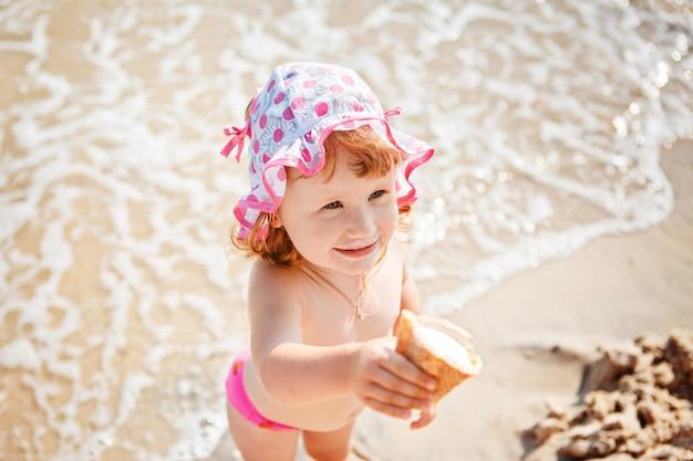 Jolie petite fille mangeant de la glace en vacances à la plage