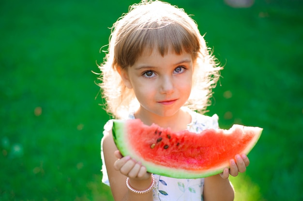 Jolie petite fille mangeant des pastèques et profitant d'un pique-nique