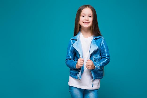 Jolie petite fille en manteau d'azur aux cheveux bruns